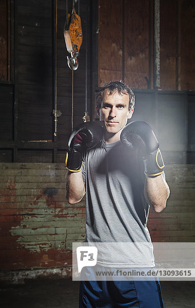 Portrait of confident male boxer standing in gym