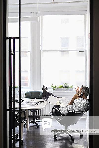 Geschäftsmann spricht am Smartphone mit erhobenen Füßen am Konferenztisch im Sitzungssaal