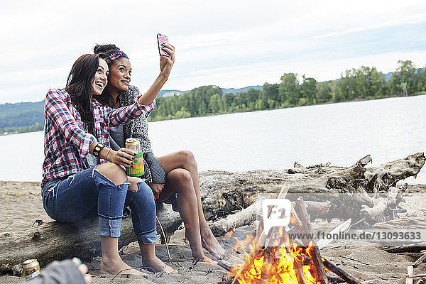 Female friends taking selfie while sitting on tree trunk by campfire against river