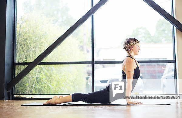 Side view of woman practicing cobra pose by window in yoga class