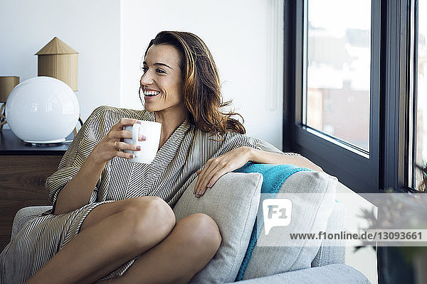 Happy woman holding cup while sitting on armchair at home