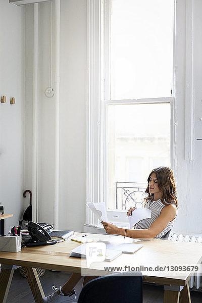 Geschäftsfrau prüft Dokumente,  während sie im Büro am Schreibtisch sitzt