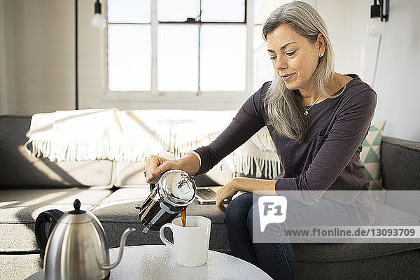 Woman pouring coffee in cup on table at home