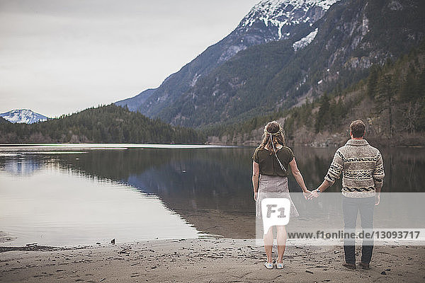 Rear view of young couple holding hands while standing at lakeshore against mountains and sky