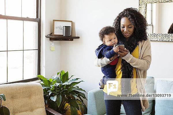 Frau mit kleinem Jungen benutzt Mobiltelefon  während sie zu Hause steht