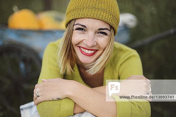 Nahaufnahme-Porträt einer lächelnden Frau mit verschränkten Armen im Park sitzend