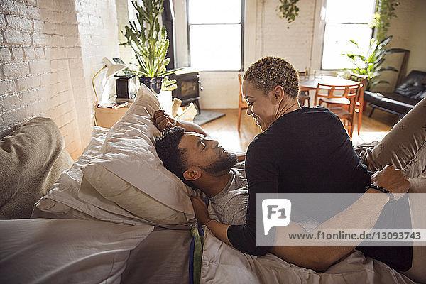 Glückliches romantisches Paar  das sich zu Hause im Bett betrachtet
