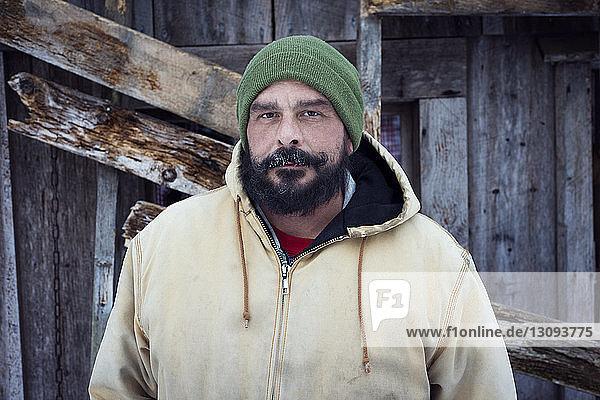 Porträt eines selbstbewussten Mannes  der vor einem Häuschen steht