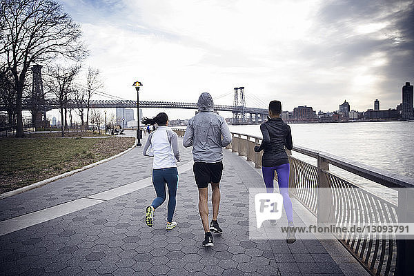 Rear view of multi-ethnic athletes running on footpath with Williamsburg Bridge in background
