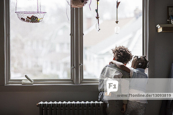 Rear view of siblings looking through window at home