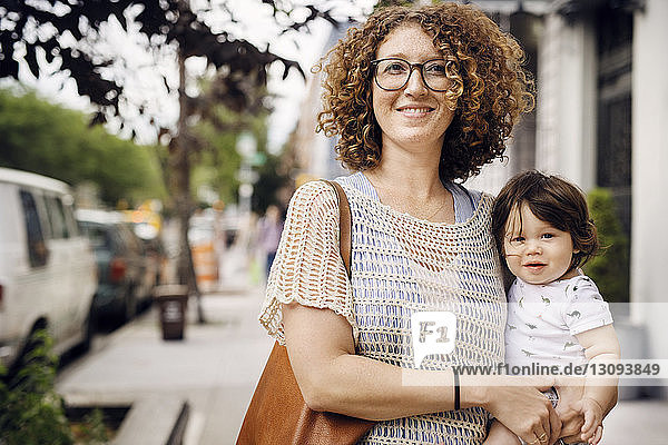 Portrait of smiling mother carrying baby boy while standing on footpath