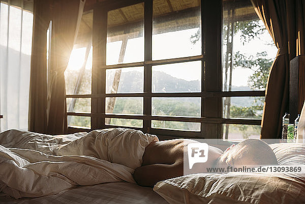 Shirtless man sleeping on bed against windows at home