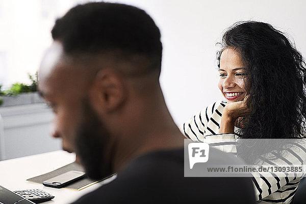 Lächelnde Geschäftsfrau arbeitet mit männlichem Amtskollegen