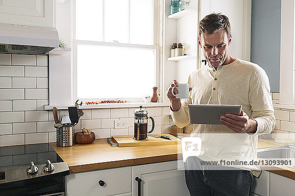 Man using tablet computer while leaning on kitchen counter at home