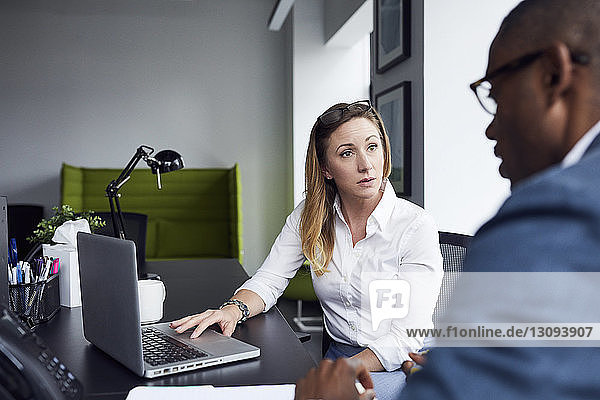 Business people discussing over laptop computer in office