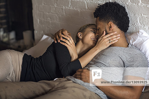 Romantic young couple lying on bed at home