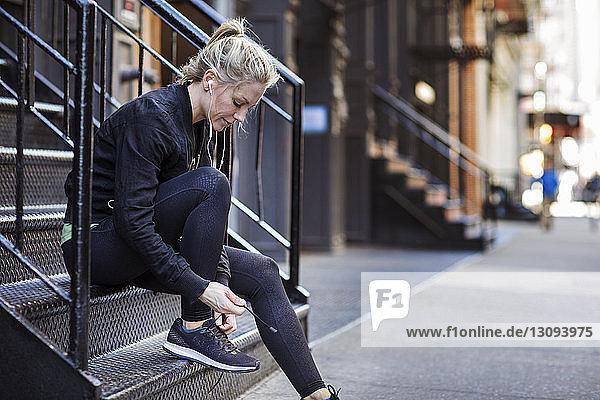 Sportlerin bindet Schnürsenkel  während sie auf Stufen in der Stadt sitzt