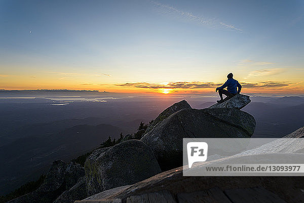 Man sitting on rock against sky at Mount Pilchuck State Park during sunset