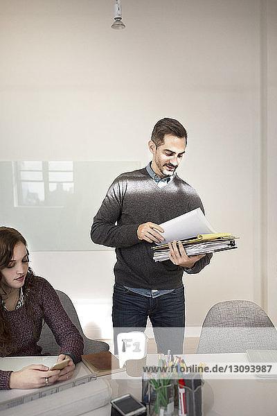 Geschäftsmann prüft Dokumente während einer Besprechung im Kreativbüro