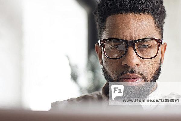 Konzentrierter Mann benutzt Laptop zu Hause