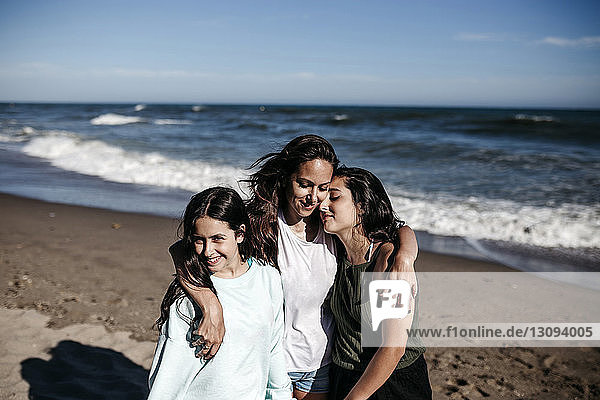Mother with daughters standing at beach against blue sky during sunny day