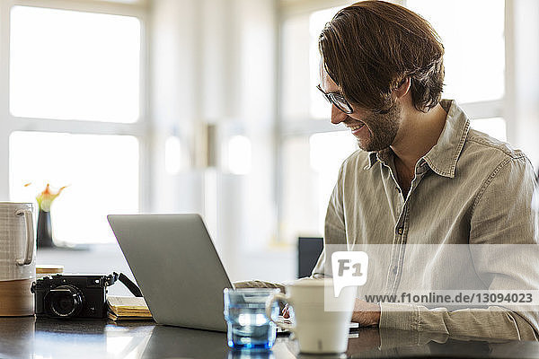 Smiling man using laptop computer on kitchen island at home