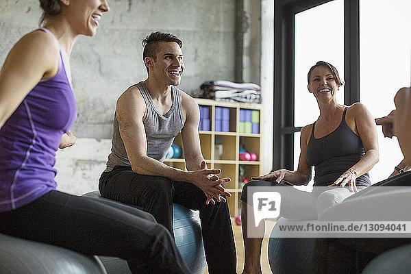 Männlicher Ausbilder spricht mit Frauen  während er in der Turnhalle auf Fitnessbällen sitzt