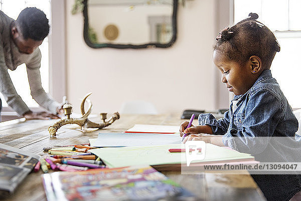 Side view of girl coloring in book with father in background at home