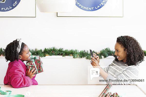 Frau fotografiert Tochter mit Weihnachtsgeschenk in der Hand  während sie am Tisch sitzt