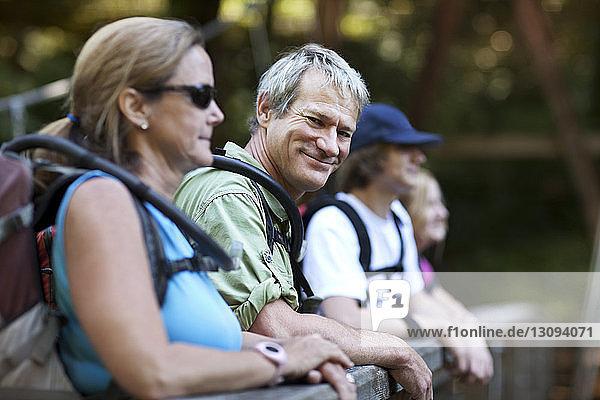 Porträt eines reifen Wanderers  der mit seiner Familie im Wald steht