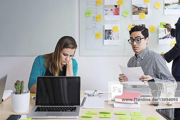 Überraschter Geschäftsmann arbeitet mit Kollege gegen Whiteboard im Büro
