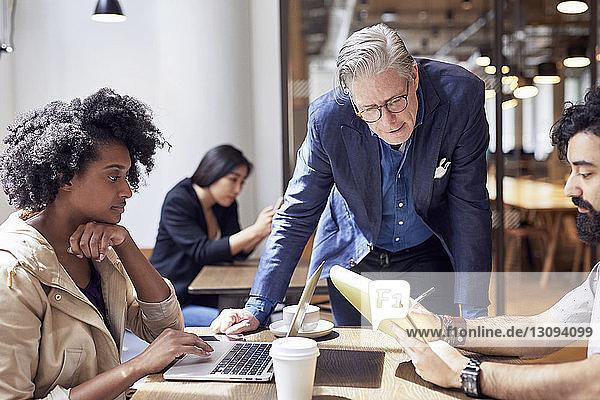 Geschäftsleute  die mit einer im Hintergrund sitzenden Kollegin arbeiten