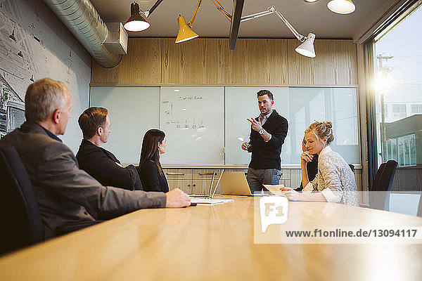 Businessman giving presentation to colleagues in board room