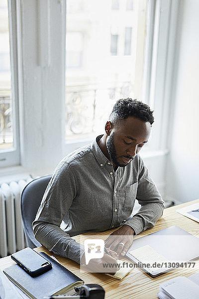 Geschäftsmann schreibt auf einem Notizblock  während er am Schreibtisch im Büro arbeitet