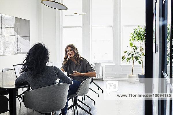 Weibliche Kollegen diskutieren,  während sie im Konferenzraum des Kreativbüros sitzen