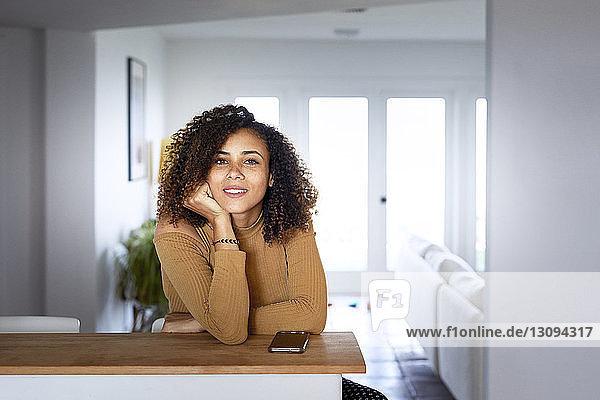 Porträt einer Frau mit Mobiltelefon auf Tisch sitzend zu Hause