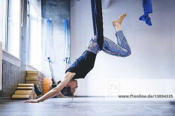 Frau hängt in Hängematte  während sie im Fitnessstudio Anti-Schwerkraft-Yoga praktiziert