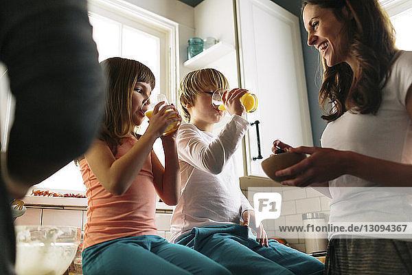 Mutter betrachtet Kinder  die Saft trinken  während sie auf der Küchentheke sitzt