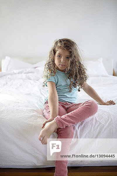 Porträt eines zu Hause auf dem Bett sitzenden Mädchens