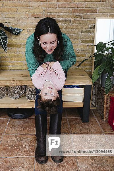 Happy mother playing with daughter while sitting on wooden table at home
