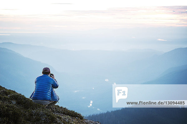 Rear view of man photographing while crouching on mountain against sky