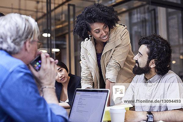 Glückliche Geschäftsfrau betrachtet männlichen Kollegen während des Treffens