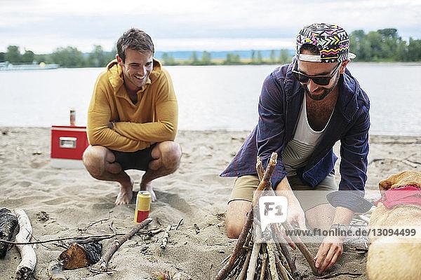 Male friends preparing for campfire