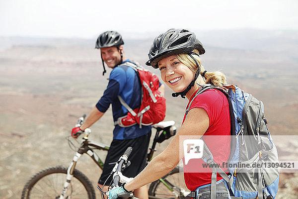 Porträt eines lächelnden Paares  das mit Fahrrädern auf einer Klippe steht