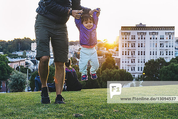 Low section of father lifting cute daughter while playing at park