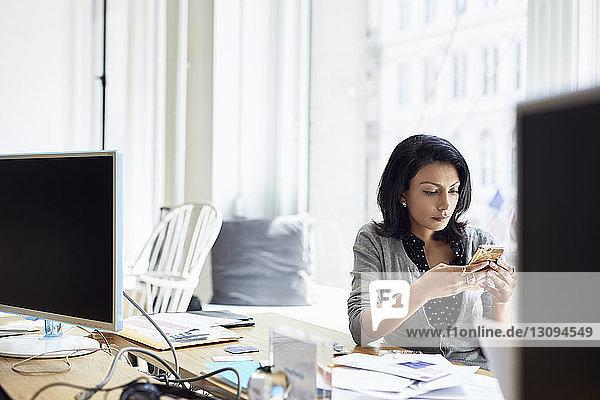 Geschäftsfrau benutzt Smartphone  während sie im Kreativbüro am Fenster sitzt