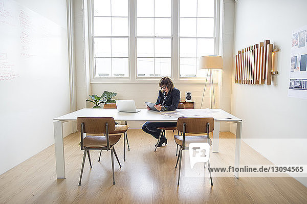 Geschäftsfrau benutzt Tablet-Computer  während sie im Büro am Schreibtisch sitzt
