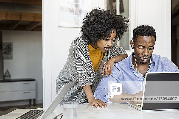 Woman looking while boyfriend using laptop computer at table