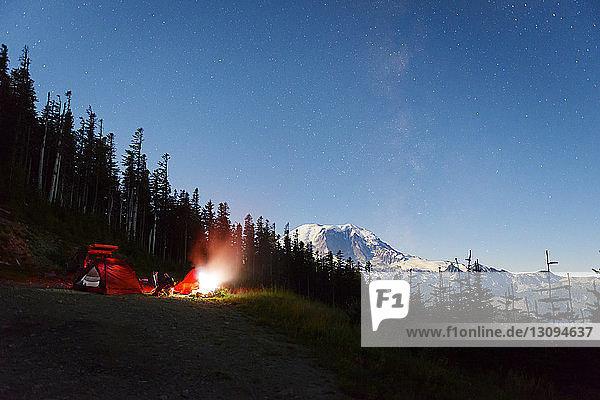 Beleuchtetes Zelt auf einem Hügel am Wald gegen den Himmel bei Nacht