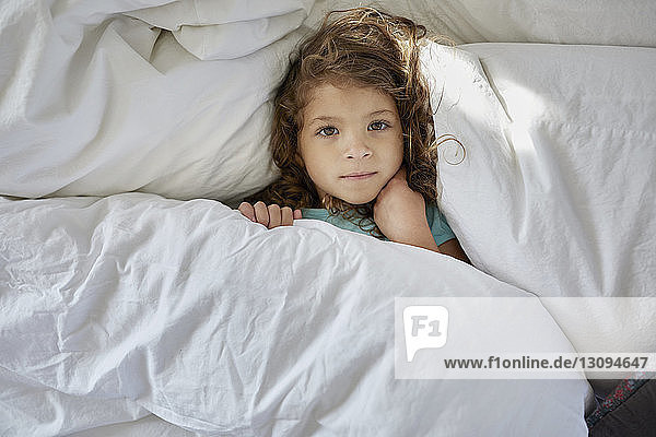 High angle portrait of girl lying on bed at home